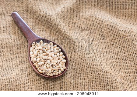 The background image of soya beans in the wooden ladle on sackcloth .