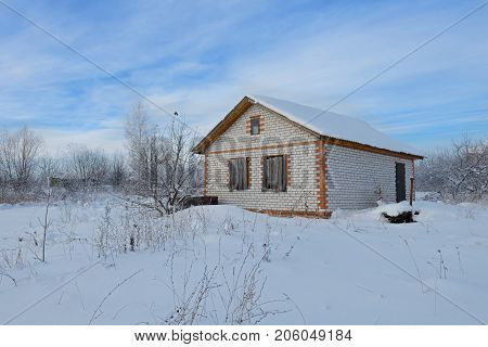 unfinished brick house on a snow-covered area in winter