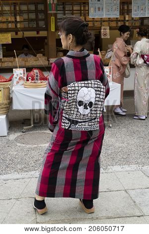 Kyoto, Japan - May 17, 2017: Woman wearing a traditional kimono with an obi that shows cats in a skull at the Yasaka jinji shrine