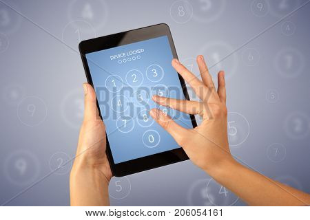 Female fingers touching tablet with locked device requiring passcode