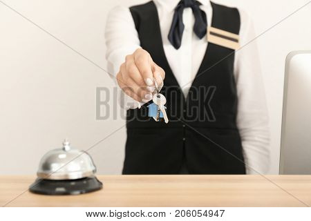 Female receptionist with room key in hotel, closeup