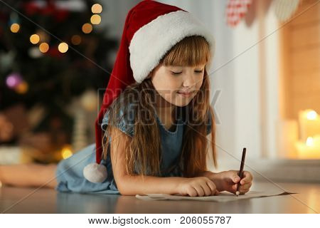 Cute girl in Christmas hat writing letter to Santa at home