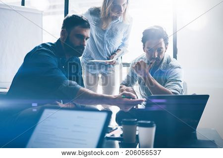 Concept of presentation new business project.Group of young coworkers discussing ideas with each other in modern office.Business people using electronic devices.Horizontal, blurred background