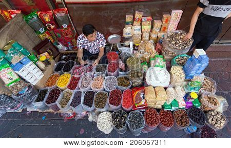 BANGKOK, THAILAND, FEBRUARY 09, 2017 : A dried fruit, mushroom and cereal seller is sitiing in the street of the Bangkok's Chinatown .