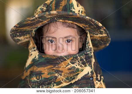PHUKET TOWN, THAILAND - MARCH 11, 2017 : A little girl is posing wearing a camo camouflage hat at the Child Watch Phuket association, for abused children .