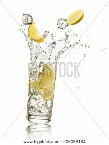glass full of water with lemon slices and ice cubes falling and splashing water on white background