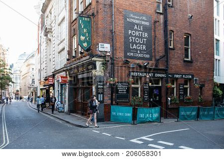 LONDON, UK - MAY 21, 2017: Tourists walking on London street outside The Lyric, a traditional English Pub in Central London.