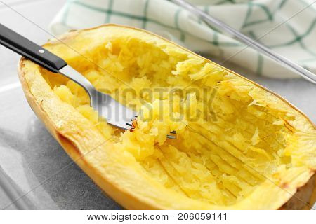 Fork with flesh in spaghetti squash, close up
