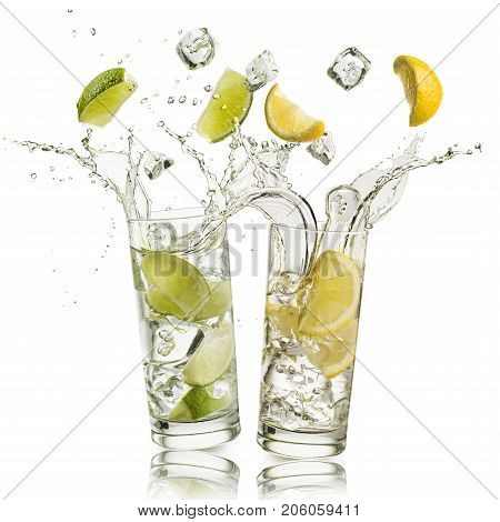 glass full of water with lemon and citron slices and ice cubes falling and splashing water on white background