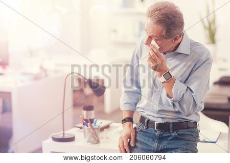Got somethink in my eye. Unhappy mature man standing in the office and using a tissue while getting an eyewinker