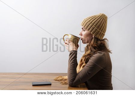 Young beautiful woman in a woolen hat drinking coffee and watching her smartphone.