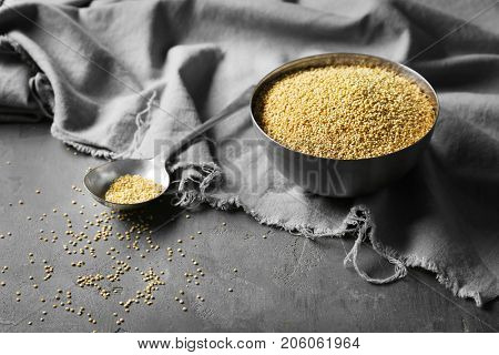 Composition with raw quinoa in metal spoon and bowl on grey background