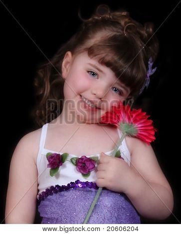 Close-up de doce menina com roupa de balé roxo e branco segurando flor brilhante. Isolado na B