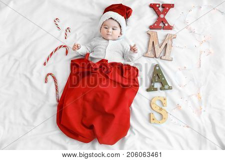 Cute baby wearing Santa hat in red bag and word XMAS made of wooden letters with Christmas lights on white sheet