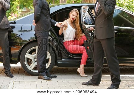 Bodyguard helping young businesswoman to get out of car