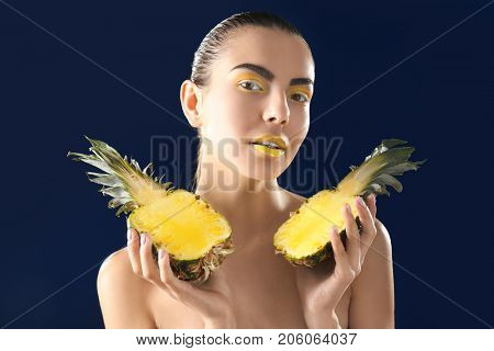Naked woman with bright makeup holding halves of pineapple on dark background