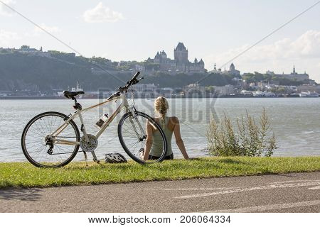 A Young Woman with Bike outside with quebec view