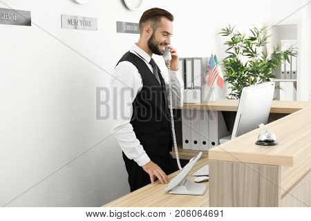 Male hotel receptionist at workplace