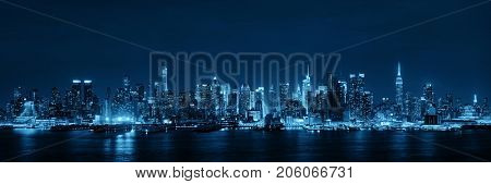 Midtown skyline over Hudson River panorama in New York City with skyscrapers at night