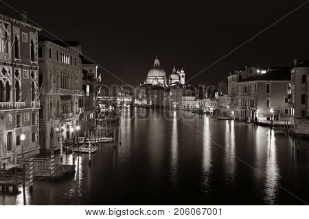 Venice canal view at night with Santa Maria della Salute and historical buildings. Italy.