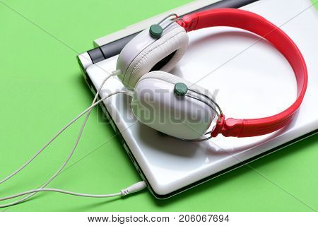 Headphones and silver laptop. Music and digital equipment concept. Electronics isolated on green background. Earphones in red and white colors made of plastic with computer. Sound recording idea.