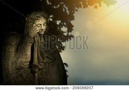 Crying angel public sculpture on the cemetery with golden sunset light