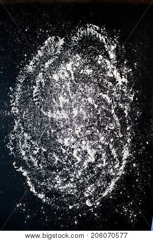 White baking flour on black slate background top view. Baking recipe concept. Wheat flour with copyspace closeup.