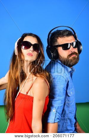 Party and music concept. Man with beard and girl sing on blue and green background. Couple in love wears headphones and sunglasses. Music fans with serious faces enjoy music stand back to back.