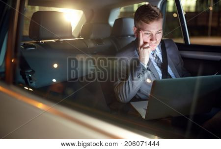 serious businessman in moving car working overtime on his laptop