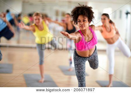 Black curly girl on body balance training at gym