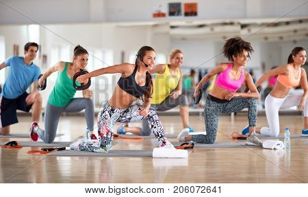 Sport group doing exercises for shaping and strengthening arms with weights in gym