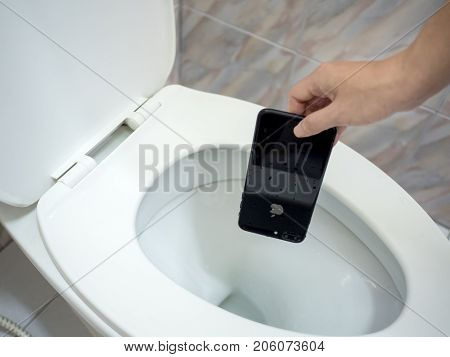 Chiangrai Thailand: August 23 2017 - Human hand picking wet Apple iPhone 7 Plus from flush toilet.