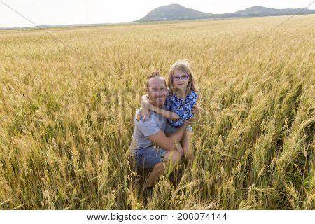 A portrait of a father and daughter playing in the wheat field at sunset.