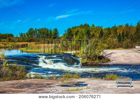 Foam water rapids on the smooth stones of the Winnipeg River. Warm autumn day. Trend of travel