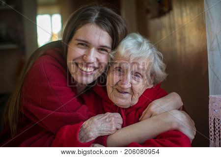 An elderly woman in an embrace with his adult daughter. Positive portrait in the house.