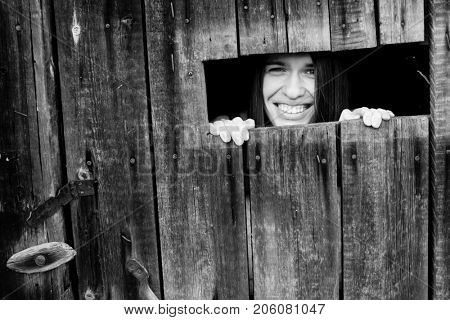 Young attractive positive woman peeking from the crack in the wooden shed.