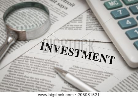 investment headline on newspaper media with magnifying glass