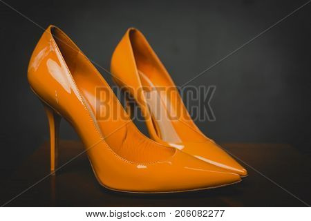 Lacquered shiny orange shoes high heels in grey background