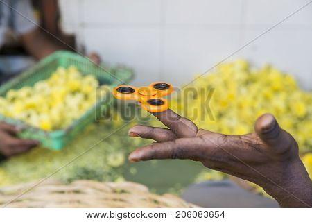 Orange hand spinner fidgeting hand man adult indian asian black hand toy