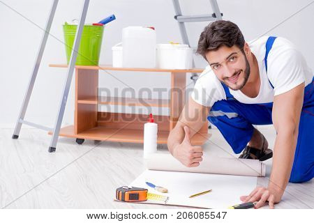 Man doing wallpaper refurbishment at home