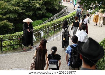 A Japanese Monk Waiting For A Donation From The Tourists And Pilgrims At Kiyomizu-dera Temple In Kyo