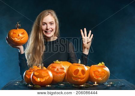 Hand countdown - number four. Happy smiling woman with Halloween pumpkins over smoky background showing four fingers