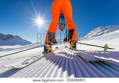 Skier posing on piste in high mountains during cold sunny day.