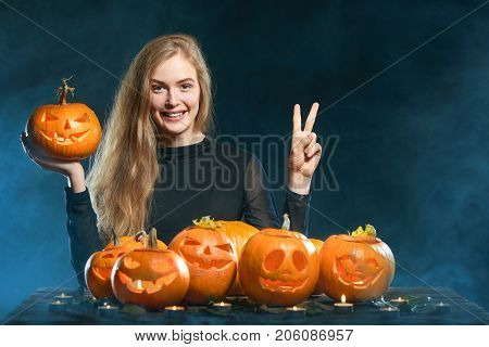 Hand countdown - number two. Happy smiling woman with Halloween pumpkins over smoky background showing two fingers