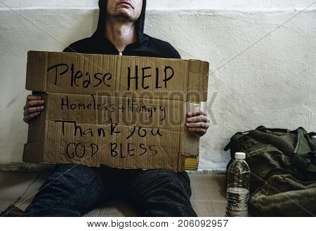 A homeless sitting holding a placard