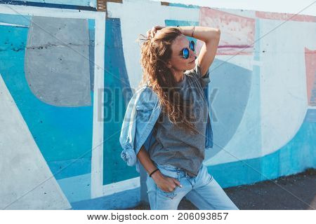 Model wearing plain gray tshirt and hipster sunglasses posing against street wall, teen urban clothing style