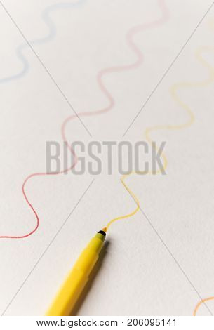 Close up of yellow highlighter painting wavy line on white paper. Lines for logo, text