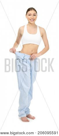 Beautiful young woman in oversized jeans on white background. Diet concept