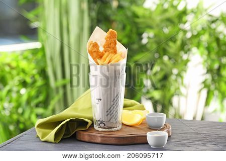 Glass with tasty fried fish and chips wrapped in paper on table