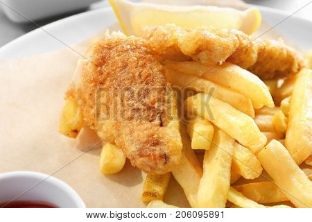 Tasty fried fish and chips on plate, closeup